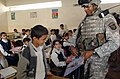 US Navy 060305-N-7586B-032 U.S. Army Sgt. Kendrick Gibson hands out school supplies, donated by children from Medora Elementary School in Jefferson County, Ky., to a class of Iraqi school children.jpg