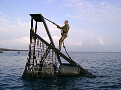 US Navy 070128-A-0000X-008 Information Systems Technician 2nd Class Brian Bell negotiates a water obstacle during the French Foreign Legion Commando course at Arta Beach in Djibouti.jpg