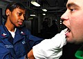 US Navy 071212-N-2735T-059 Hospital Corpsman 2nd Class Antoinette Peterson takes a swab sample from Aviation Machinist's Mate 3rd Class Roger Cunningham to submit for a bone marrow drive aboard the amphibious assault ship USS N.jpg