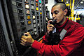 US Navy 090306-N-1525H-024 Aviation Ordnanceman Airman Joel Jeffries, assigned to Weapons Department's G-1 division, speaks through an X30J8 sound powered telephone during a weapons movement.jpg