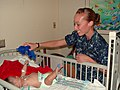 US Navy 091005-N-2888Q-003 Hospital Corpsman 2nd Class Amanda Valenzuela, assigned to Navy Operational Support Center Albuquerque, gives an infant a Navy bear as part of a Caps For Kids visit to the pediatric department of Pres.jpg