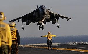 US Navy 120131-N-ZZ999-080 Aviation Boatswain's Mate (Handling) 1st Class Andre Hardin guides an AV-8B Harrier onto the flight deck of the amphibio.jpg