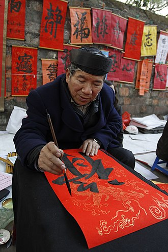 "History of writing in Vietnam - A calligrapher writing the Chinese character 祿 ""good fortune"" (Sino-Vietnamese reading: lộc) in preparation for Tết, at the Temple of Literature, Hanoi (2011)"