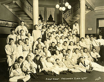 About 50 members of the 1935 freshman class gather on the first floor of their dormitory, which has columns, a chandelier with spherical lights, and multiple staircases.