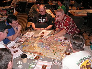 Six men sit around a table, studying the contents atop it. On the table are a map, many small cardboard chits (counters), and cards. One man has his left hand hovering above the map, finger pointing at a stack of counters.