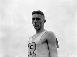 A young man dressed in a white singlet with the letter 'R' on the front