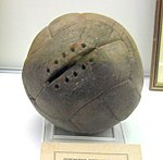 A worn, old brown football. One panel has space for stitches, but none are present.