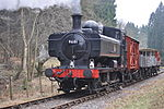 A black pannier tank locomotive is passing along a single track through woodland. The locomotive is pulling a train of a covered red wagon, three grey open wagons, and a red guard's van.