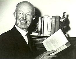 Head-and-shoulders informal portrait of bald man with moustache, holding an open book