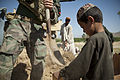 A U.S. Marine with a Marine special operations team, left, helps an Afghan boy fill a sandbag during a construction project for an Afghan Local Police (ALP) checkpoint in Helmand province, Afghanistan, March 30 130330-M-BO337-068.jpg
