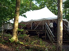 Photo of a large white tent on a wooden platform with stairs leading up to it.