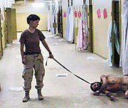"Pfc. England holding a leash attached to a prisoner collapsed on the floor, known to the guards as ""Gus"""
