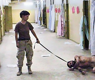 "Abu Ghraib torture and prisoner abuse - Lynndie England holding a leash attached to a prisoner, known to the guards as ""Gus"""
