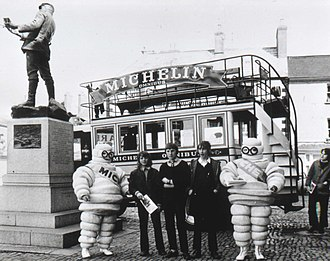 Michelin - c. 1965–1970, view of old fashioned Michelin omnibus and two michelin men with bystanders behind Charles Rolls statue, Monmouth, Wales.