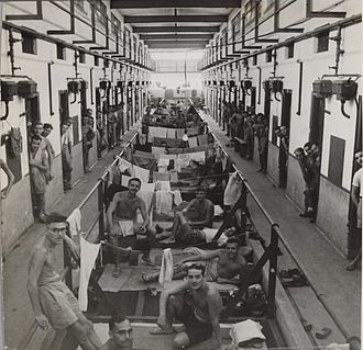 Changi Prison - Liberated Allied prisoners lying in a corridor and looking out of cell doorways in Changi Prison, c. 1945