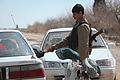 An Afghan National Civil Order Police (ANCOP) officer shakes hands with a man passing through a vehicle security checkpoint, Marjah, Afghanistan, Feb 120224-M-JI376-017.jpg