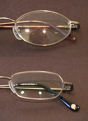 Anti-reflective coating - Uncoated glasses lens (top) versus lens with antireflective coating. Note the tinted reflection from the coated lens.