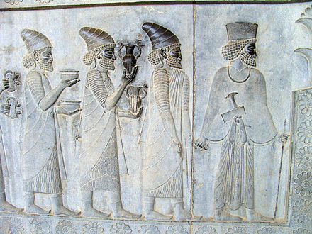 "Objects in the ""Apadana"" reliefs at Persepolis: armlets, bowls, and amphorae with griffin handles are given as tribute. Apadana Persepolis Iran.JPG"