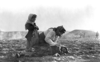 Armenian deportees near Aleppo during the Armenian Genocide, 1915 Armenian woman kneeling beside dead child in field.png