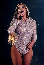 A woman holding a microphone, wearing a bodysuit