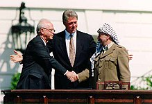 A man in a dark suit on the left shakes the hand of a man in traditional Arab headdress on the right. Another man (Bill Clinton) stands with open arms in the center behind them.