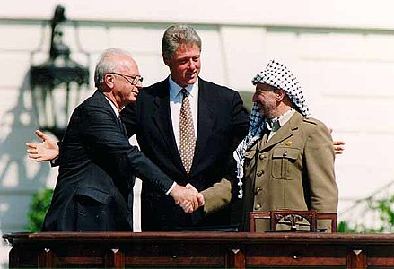 Yitzhak Rabin, Prime Minister of Israel and leader of the Israeli Labor Party, shaking hands with Yasser Arafat, Chairman of the Palestinian Liberation Organization and founder of Fatah, in front of United States president Bill Clinton after having signed the Oslo Accords in 1993 Bill Clinton, Yitzhak Rabin, Yasser Arafat at the White House 1993-09-13.jpg