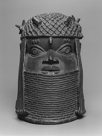 Benin ancestral altars - This cast-brass head, from the collection of the Brooklyn Museum, would have been commissioned for a royal altar in Benin. Its relative naturalism and shiny surface make it both beautiful and frightening, appropriate attributes for a powerful monarch. The coral-beaded crown and collar represent the regalia worn by reigning obas.