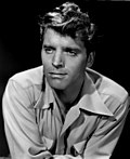 Black and white publicity photo of Burt Lancaster--a handsome white man with light eyes and wavy light-colored hair, oval face, wearing a light-colored shirt, around 34 years of age--in 1947.