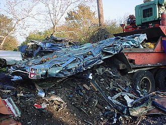 Car crusher - a blue 1990s Lincoln Town Car after crushing