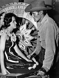 Lucas McCain looking at woman sitting in front of roulette wheel.