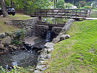 A wooden bridge over a small dam over which water falls into a stream flowing out of the picture at lower left. Behind it is a large, still pond; to the left a black sport-utility vehicle is parked