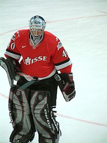 An ice hockey goaltender skates on ice. He is wearing a red and white sweater, and black and grey pads.