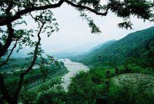 Photographie du système d'irrigation de Dujiangyan. Les voies d'eau sont visibles au fond d'une vallée bordée de montagnes verdoyantes sur la droite.