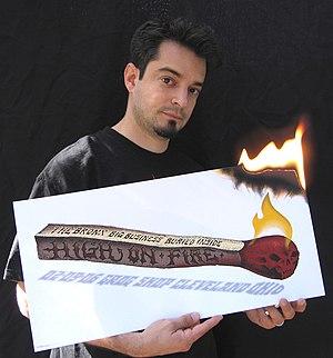 """Emek - Emek Golan holds his gig poster for """"High On Fire"""""""