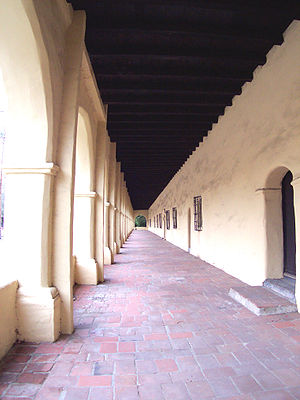 Mission Revival architecture - 1797 Mission San Fernando Rey de España: View looking down an exterior arcade or corredor, an element frequently used in Mission Revival design.