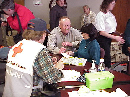 FEMA Director Joe M. Allbaugh talks with a disaster victim at the Red Cross Shelter in Enid during a tour of damage areas in Oklahoma. FEMA - 5745 - Photograph by Gene Romano taken on 02-07-2002 in Oklahoma.jpg