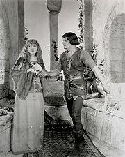 Douglas Fairbanks as Robin Hood giving Enid Bennett as Maid Marian a dagger