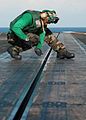 Filing down burs aboard the USS George Washington DVIDS128356.jpg