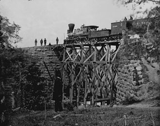 Military logistics - US Military Railroad engineers monitor the first use of a wooden trestle they have hastily built to replace the masonry bridge destroyed by Confederates, O&A railroad, Northern Virginia, c. 1863