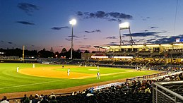 A view of the green baseball field from the third base side seats showing men in white baseball uniforms playing their positions as the sun has just set behind first base