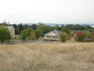 Fort Lawton - In the Historic District, looking toward Puget Sound. The visible buildings are, left to right, the Band Barracks, Guard House and Quartermasters Stables.