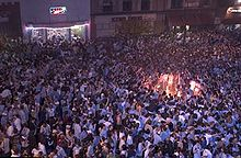 A large gathering of people on a street with a bonfire in the right side of the image.