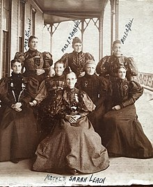 "Eight women in Victorian-style dresses posing for a photo in front of a building. The woman in front and center is labeled with handwriting as ""Mother Sarah Leach"". The remaining seven woman form two rows behind Mrs. Leach. The three woman in the back row are also labeled in handwriting from left to right, ""Mrs. Killion, Mrs. F.P. Sargent, and Mrs. E.A. Ball""."