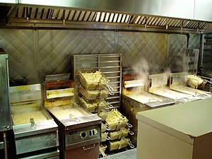 A row of five deep fryers, all steaming and filled with baskets of French fries.