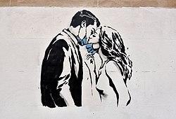 ett par kysser medan de drar åt sidan sina skyddande ansiktsmasker