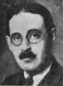 Black and white portrait photo of a white male with dark hair, glasses and a mustache