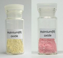 Samples of holmium(III) oxide under ambient light, and trichromatic light
