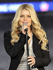 Jessica Simpson holding a microphone while singing