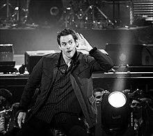 Photographie en noir et blanc de Jim Carrey en plein spectacle, il porte la main à son oreille comme pour mieux entendre
