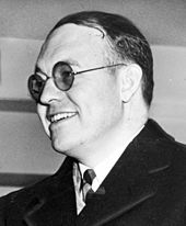 Smiling man in round-rimmed glasses
